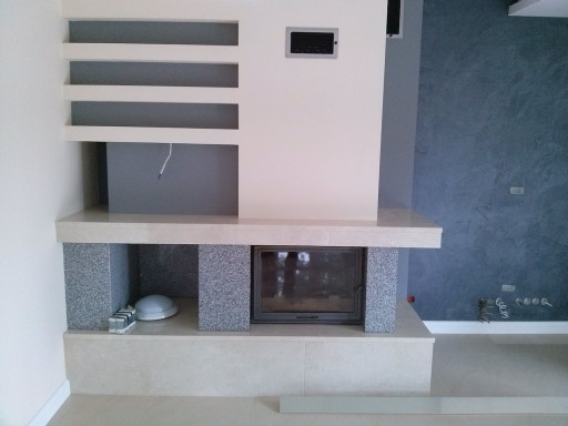 FIREPLACE made of crema marfil marble with elements of grey granite