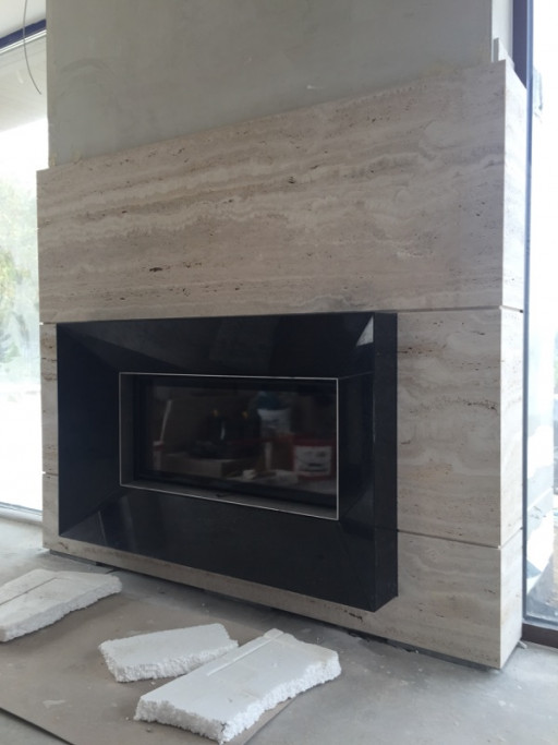 FIREPLACE made from classico romano travertine combined with black granite
