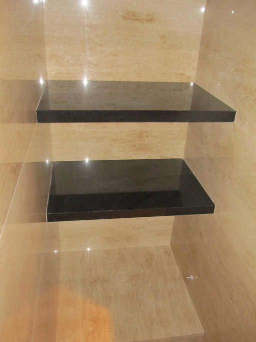 Wall shelves - wall made of breccia marble and shelves made of absolute black granite